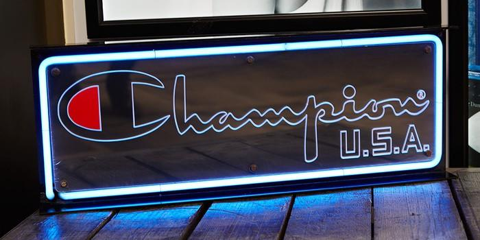 The Champion U.S.A. logo displayed in bright neon lights on a store sign.