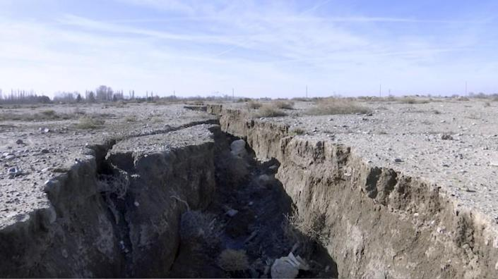 This frame grab from video taken on Jan. 8, 2019, shows fissure in the land caused by drought and excessive water pumping, in Malard, west of Tehran, Iran. Fissures appear along roads, while massive holes open up in the countryside, their gaping maws a visible sign from the air of something Iranian authorities now openly acknowledge: The area around the capital Tehran is literally sinking. (AP Photo)