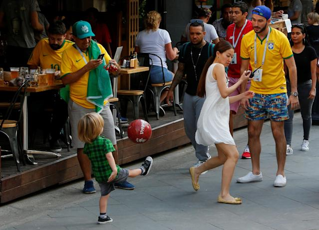 Brazil fans play with a ball with children as they celebrate Brazil's victory over Costa Rica at the World Cup Group E soccer match in central Moscow, Russia June 22, 2018. REUTERS/Sergei Karpukhin