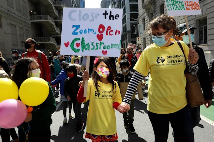 Kristina Leng, 9, marches to the Civic Center with her mother Monika Leng, and father Rodney Leng during the Families Rally to Demand Schools Fully Reopen event in San Francisco, on March 13, 2021.dent, marches to the Civic Center as she holds hands with her mother Monika Leng, and father Rodney Leng during the Families Rally to Demand Schools Fully Reopen event in San Francisco, on March 13, 2021.