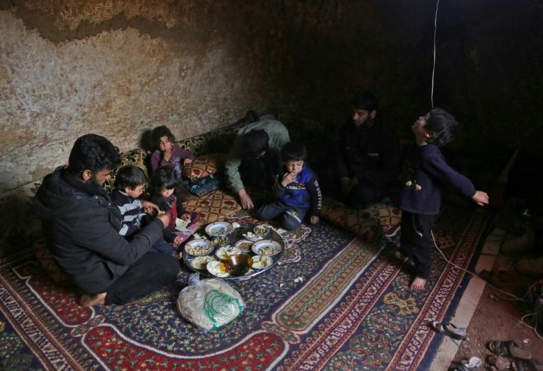 Darra lays down a large carpet for the family to share a frugal meal on the bare earth of the underground shelter (AFP Photo/Aref TAMMAWI)