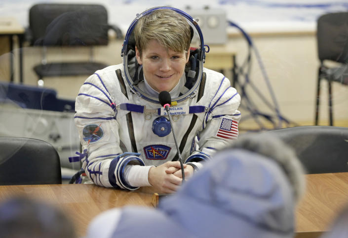 U.S. astronaut Anne McClain, member of the main crew of the expedition to the International Space Station (ISS), speaks with her relatives through a safety glass prior to the launch of Soyuz MS-11 space ship at the Russian leased Baikonur cosmodrome, Kazakhstan, Monday, Dec. 3, 2018. (AP Photo/Dmitri Lovetsky, Pool)