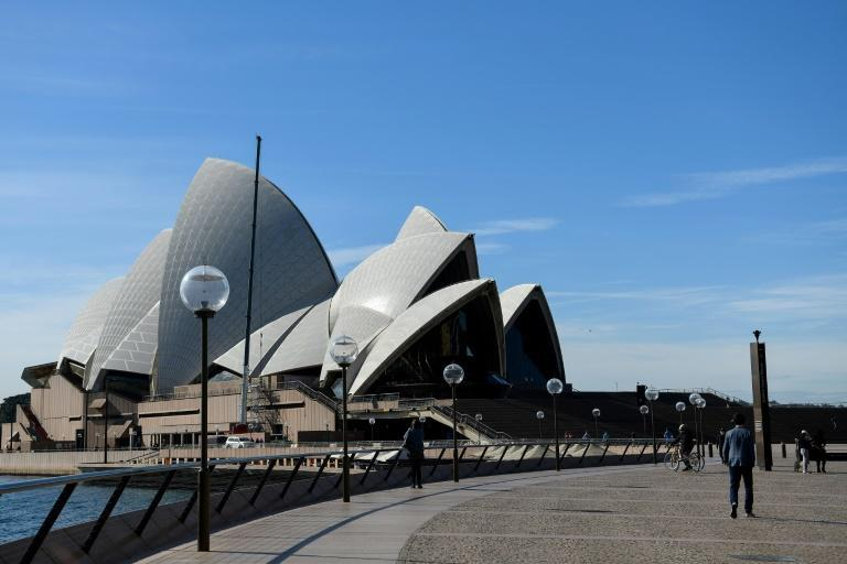 People walk through an unusually quiet Sydney Opera House forecourt in Sydney, as the city remains in lockdown for a second week