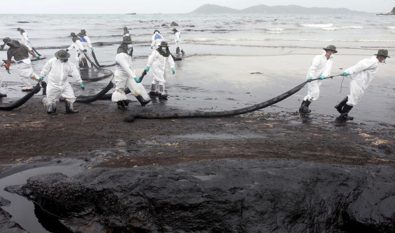 Workers remove crude oil during a clean up operation on the beach of Prao Bay on Samet Island in Rayong province eastern Thailand Tuesday, July 30, 2013. About 50,000 liters (13,200 gallons) of crude oil that leaked from a pipeline operated by PTT Global Chemical Plc, has reached the popular tourist island in Thailand's eastern sea despite continuous attempts to clean it up. (AP Photo)