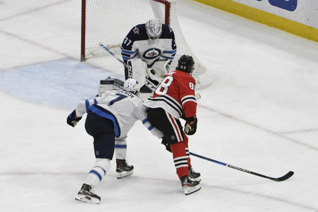 Winnipeg Jets goaltender Connor Hellebuyck (37) makes a save on Chicago Blackhawks right wing Patrick Kane (88) during the second period of an NHL hockey game Sunday, Jan. 19, 2020, in Chicago. (AP Photo/David Banks)