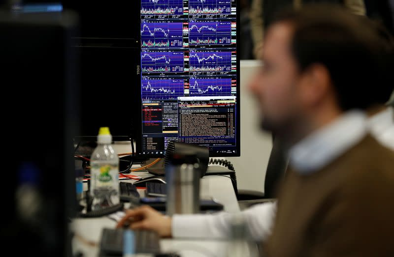Financial traders work at their desks at CMC Markets in the City of London