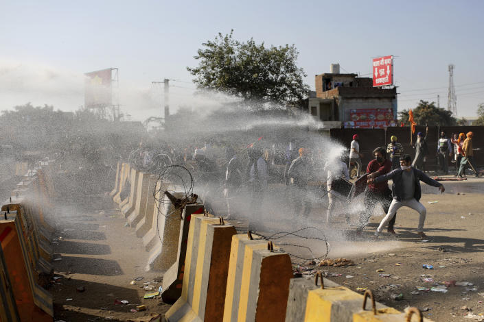 Police use water cannon to disperse protesting farmers, as they attempt to move towards Delhi, at the border between Delhi and Haryana state, Friday, Nov. 27, 2020. Thousands of agitating farmers in India faced tear gas and baton charge from police on Friday after they resumed their march to the capital against new farming laws that they fear will give more power to corporations and reduce their earnings. While trying to march towards New Delhi, the farmers, using their tractors, cleared concrete blockades, walls of shipping containers and horizontally parked trucks after police had set them up as barricades and dug trenches on highways to block roads leading to the capital. (AP Photo/Altaf Qadri)