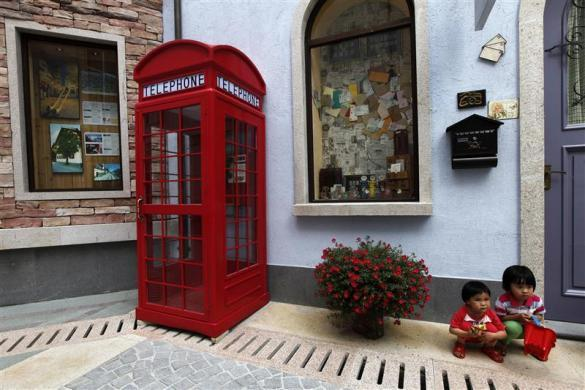 Children pose for pictures at the replica of Austria's UNESCO heritage site, Hallstatt village, in China's southern city of Huizhou in Guangdong province, June 1, 2012.