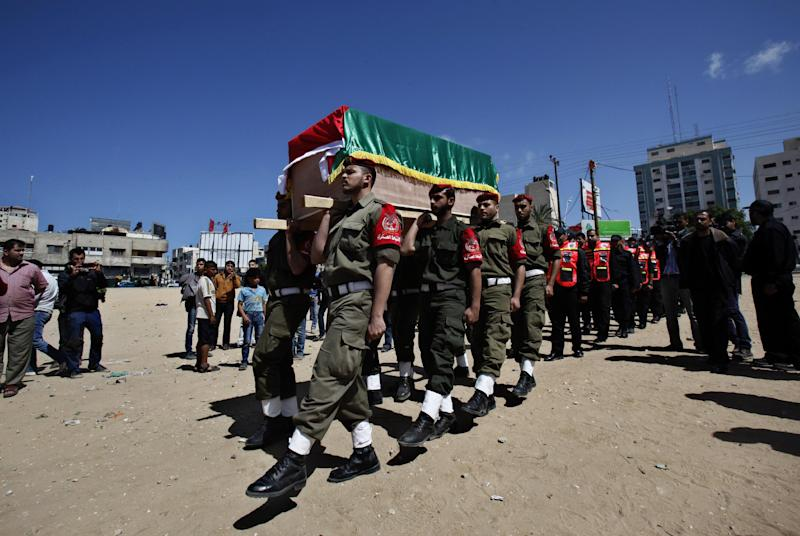 Palestinian Hamas security police officers carry a mock coffin of Maysara Abu Hamdiyeh during a symbolic funeral in Gaza City, Thursday, April 4, 2013. Abu Hamdiyeh, 64, who was serving a life sentence for his role in a foiled attempt to bomb a busy cafe in Jerusalem in 2002, died Tuesday of cancer in an Israeli jail. (AP Photo/Adel Hana)