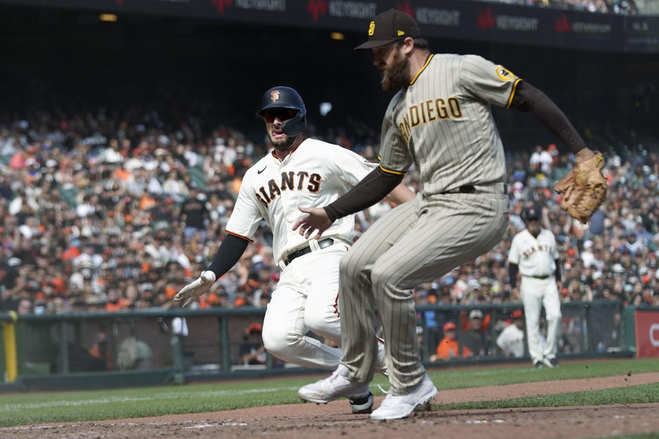 San Francisco Giants' Kris Bryant, left, slides home to score past San Diego Padres pitcher Austin Adams during the sixth inning of a baseball game in San Francisco, Thursday, Sept. 16, 2021. (AP Photo/Jeff Chiu)