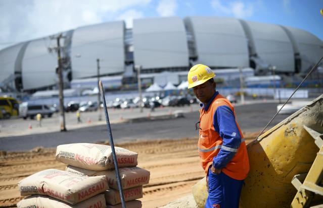 A construction worker rests in the midday sun next to the Dunas arena soccer stadium in Natal, June 12 , 2014. Mexico will face Cameroon in their 2014 World Cup football match here on June 13. REUTERS/Dylan Martinez (BRAZIL - Tags: BUSINESS CONSTRUCTION SOCCER SPORT WORLD CUP)