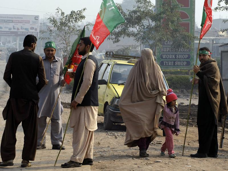 In this photo taken on Monday, Dec. 16, 2013, workers of Pakistan Tehreek-e-Insaf headed by cricketer-turned-politician Imran Khan stand at a highway to stop NATO trucks carrying supplies to neighboring Afghanistan, in Peshawar, Pakistan. U.S. officials, frustrated that hundreds of military shipments heading out of Afghanistan have been stopped on the land route through Pakistan because of anti-American protests, face the possibility of flying out equipment at an additional cost of $1 billion. (AP Photo/Mohammad Sajjad)