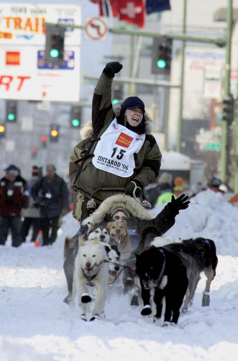 """Author Gary Paulsen, from Tularosa, N.M., cheers he drives his dog team down Fourth Avenue with Carole Markell, from Temple City, Calf., in the sled, during the ceremonial start of the Iditarod Trail Sled Dog Race Saturday, March 4, 2006, in Anchorage, Alaska. Among the many books Paulsen wrote are """"Winterdance: The Fine Madness of Running the Iditarod"""" and """"My Life in Dog Years."""""""