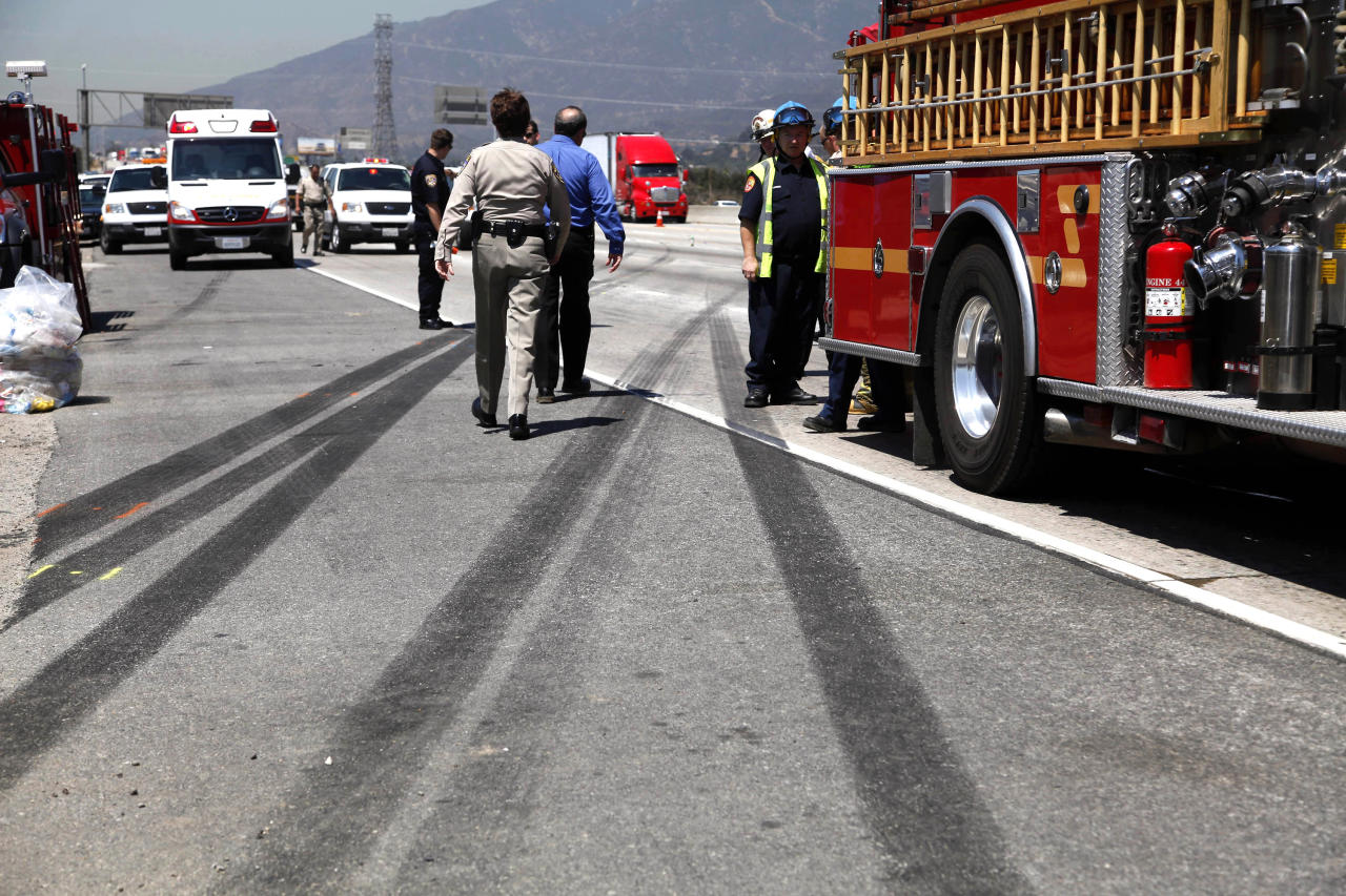 Officials investigate the scene of an accident along Interstate 210 in Irwindale, Calif. on Thursday, Aug 22, 2013. A tour bus carrying gamblers to an Indian casino overturned on the Southern California freeway injuring more than 50 people on board. The bus went through a chain-link fence off the side of the road and ended up on its side down a dirt embankment between the freeway and railroad tracks. (AP Photo/Nick Ut)