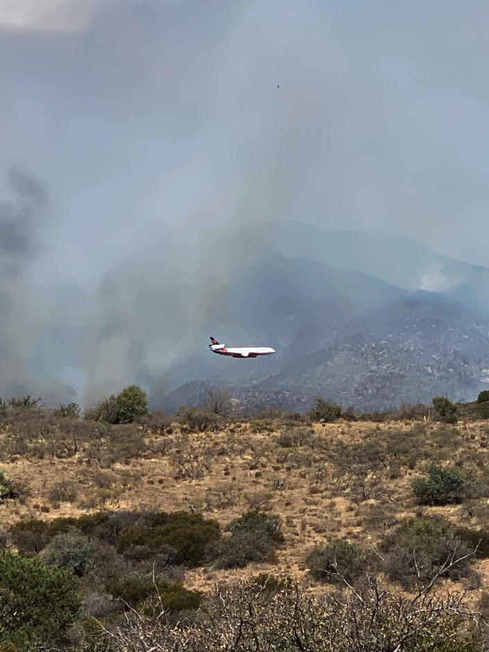 This Tuesday, June 8, 2021, photo provided by Arizona Rep. David Cook, a rancher who lives out of Globe, Ariz., shows an aerial tanker preparing to drop fire retardant on a wildfire threatening area homes and ranches. Firefighters in Arizona were fighting Tuesday to gain a foothold into a massive wildfire, one of two that has forced thousands of evacuations in rural towns and closed almost every major highway out of the area. (David Cook via AP)