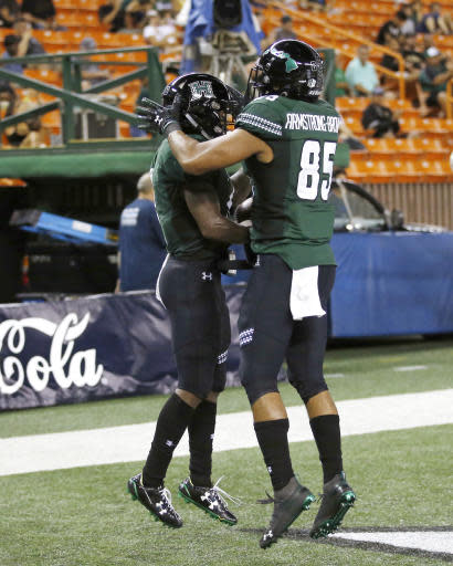 After making a touchdown over Duquesne, Hawaii wide receiver Cedric Byrd (6) celebrates with wide receiver Marcus Armstrong-Brown (85) during the second quarter of an NCAA college football game Saturday, Sept. 22, 2018, in Honolulu. (AP Photo/Marco Garcia)