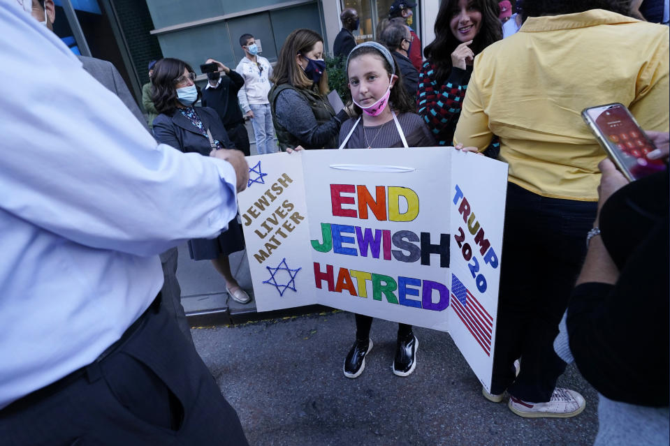 """A young girl holds a poster she made as she prepares to pose for a cell phone photograph for a relative as she and others joined protesters outside the offices of New York Gov. Andrew Cuomo, Thursday, Oct. 15, 2020, in New York. Three Rockland County Jewish congregations are suing New York state and Cuomo, saying he engaged in a """"streak of anti-Semitic discrimination"""" with a recent crackdown on religious gatherings to reduce the state's coronavirus infection rate. (AP Photo/Kathy Willens)"""