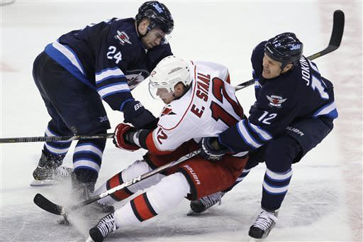 Winnipeg Jets' Grant Clitsome (24) and Olli Jokinen (12) double-team Carolina Hurricanes' Eric Staal (12) during the second period of their NHL hockey game in Winnipeg, Manitoba, Thursday, April 18, 2013. (AP Photo/The Canadian Press, John Woods)