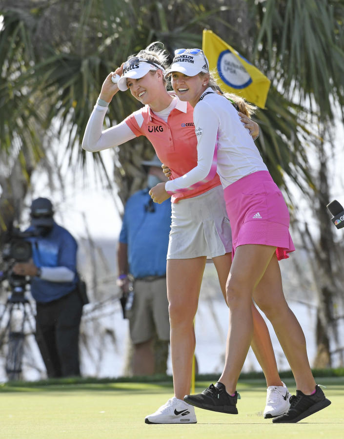 Nelly Korda, left, celebrates with her sister Jennifer, right, walking off the 18th green after winning the Gainbridge LPGA golf tournament Sunday, Feb. 28, 2021, in Orlando, Fla. (AP Photo/Stan Badz)