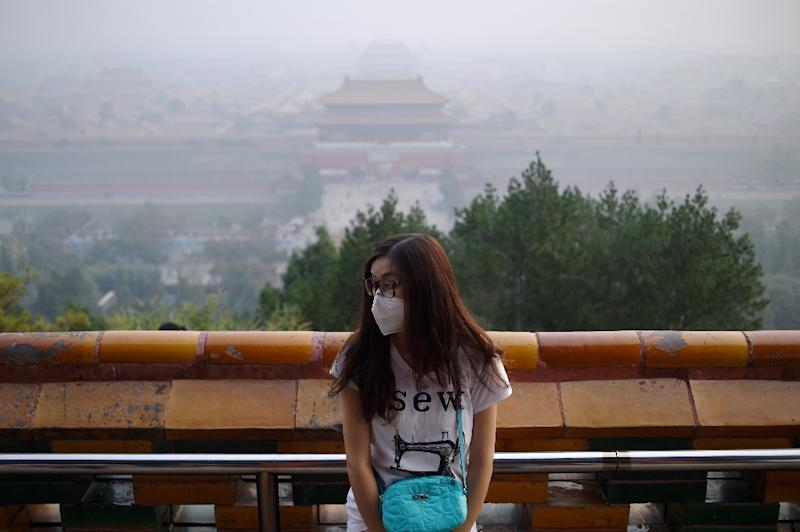 A woman wears a mask as she visits a park near the Forbidden City shrouded in haze in Beijing on October 7, 2015 (AFP Photo/Wang Zhao)
