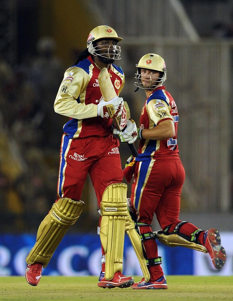 Royal Challengers Bangalore batsman AB de Villiers (R) and Chris Gayle run between the wickets during the IPL Twenty20 cricket match between Kings XI Punjab and Royal Challengers Bangalore at PCA Stadium in Mohali on April 20, 2012.  RESTRICTED TO EDITORIAL USE. MOBILE USE WITHIN NEWS PACKAGE    AFP PHOTO/ Prakash SINGH (Photo credit should read PRAKASH SINGH/AFP/Getty Images)