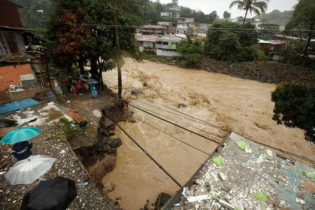 People look at a street collapsed by the Tiribi river flooded by heavy rains from Tropical Storm Nate in San Jose, Costa Rica October 5, 2017. REUTERS/Juan Carlos Ulate