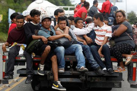 Honduran migrants, part of a caravan trying to reach the U.S., are seen on a truck during a new leg of her travel in Zacapa