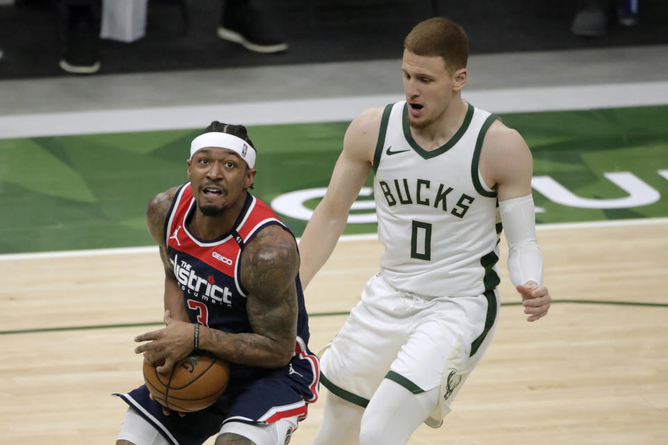 Washington Wizards' Bradley Beal, left, drives to the basket against Milwaukee Bucks' Donte DiVincenzo during the first half of an NBA basketball game Wednesday, May 5, 2021, in Milwaukee. (AP Photo/Aaron Gash)