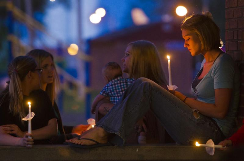Shona Osladil, of Ottawa, holds a candle during a prayer vigil for Lana-Leigh Bailey and the other victims at Forest Park Friday, May 10, 2013 in Ottawa, Kan. Kyle Flack, a 27-year-old convicted felon was charged Friday in the deaths of a woman and two men whose bodies were found at an eastern Kansas farm home earlier this week, according to a criminal complaint. (AP Photo/The Kansas City Star, Allison Long)