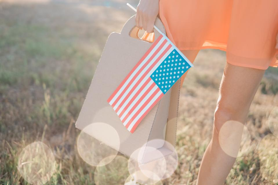 Memorial day sale, Independence day sale. Female hand with paper bag and american flag in spring or summer park