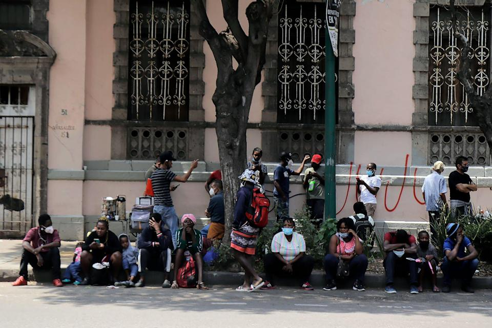 Haitian migrants sit on the pavement outside the Mexican Commission for Refugee Support in Mexico City