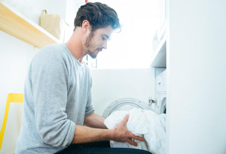 Man at home doing laundry, putting clothes in the washing machine.