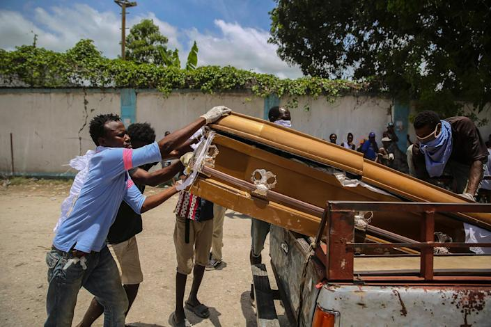 """Men load the coffin containing the remains of Francois Elmay, after recovering his body from the rubble of a home, in Les Cayes on Aug. 18.<span class=""""copyright"""">Joseph Odelyn—AP</span>"""