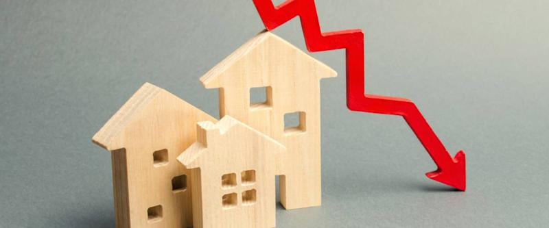 Miniature wooden houses and a red arrow down. Lower mortgage interest rates.