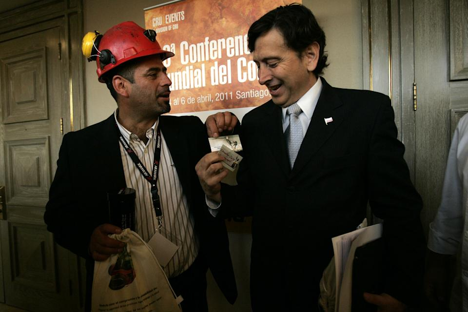 Laurence Golborne (R), Chile's Minister of Mining and Energy, and Mario Sepulveda, one of the 33 miners trapped underground at a mine some two months, talk as they attend the World Copper Conference opening ceremony at Santiago April 5, 2011. REUTERS/Victor Ruiz Caballero (CHILE - Tags: BUSINESS POLITICS)