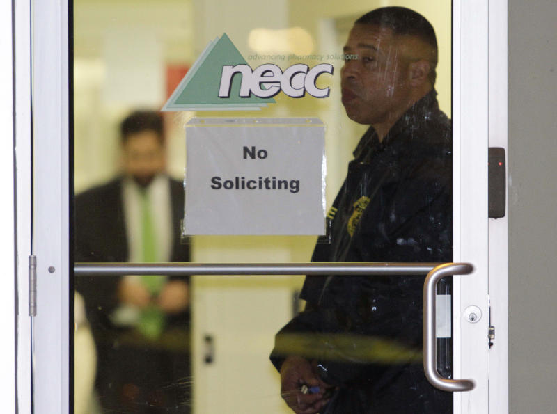 A Food and Drug Administration Agent stands at the doorway of New England Compounding Center in Framingham, Mass., Tuesday, Oct. 16, 2012, as investigators work inside. The company's steroid medication has been linked to a deadly meningitis outbreak. FDA spokesman Steven Immergut says the visit is part of the investigation into the outbreak, which has killed at least 15 people and sickened more than 200 others in 15 states. (AP Photo/Bill Sikes)