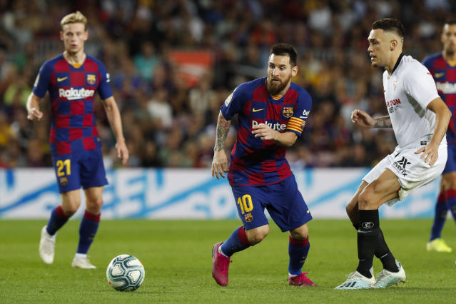 Barcelona's Lionel Messi, center, runs with the ball during Spanish La Liga soccer match between Barcelona and Sevilla at the Camp Nou stadium in Barcelona, Sunday, Oct. 6, 2019. Messi scored once in Barcelona's 4-0 victory. (AP Photo/Joan Monfort)