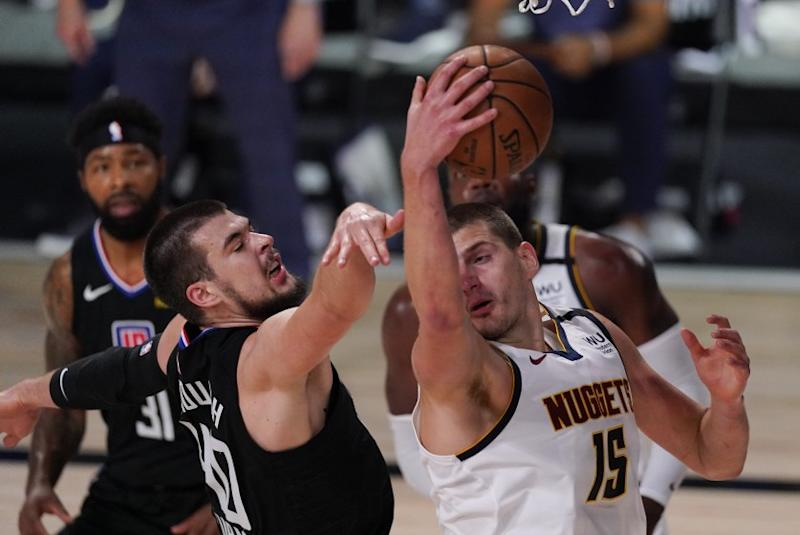 The Clippers' Ivica Zubac, left, battles the Nuggets' Nikola Jokic for a rebound Sept. 5, 2020.