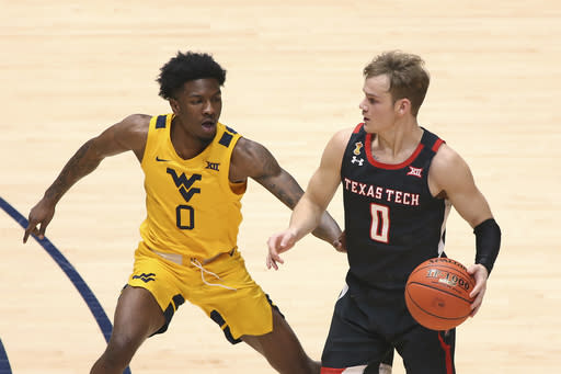Texas Tech guard Mac McClung, right, is defended by West Virginia guard Kedrian Johnson, left, during the second half of an NCAA college basketball game Monday, Jan. 25, 2021, in Morgantown, W.Va. (AP Photo/Kathleen Batten)