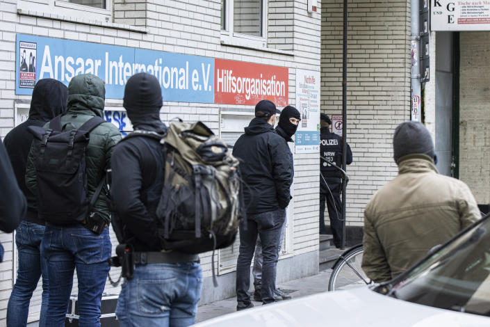 Police officers stay in front of a building of the Ansaar International association in Duesseldorf, Germany, Wednesday, May 5. 2021. The German government on Wednesday banned the Muslim organization. Buildings in 10 German states were raided, according to German news agency dpa, which said that the donations Ansaar collected were donated to welfare projects but also to groups such as Al-Nusra in Syria, the Palestinians' Hamas group and Al-Shabaab in Somalia. (Marcel Kusch/dpa via AP)