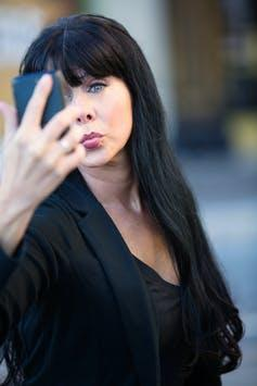 A woman puckers her lips while taking a selfie.