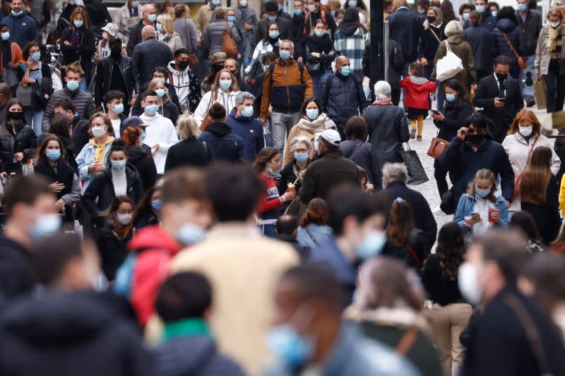 People wearing protective face masks walk in a street of Nantes