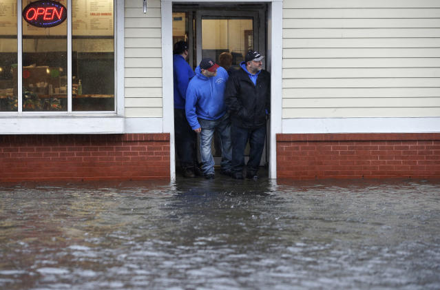 <p>People stand at the entrance to a pizza shop as water floods a street, in Scituate, Mass., Friday, March 2, 2018. (Photo: Steven Senne/AP) </p>