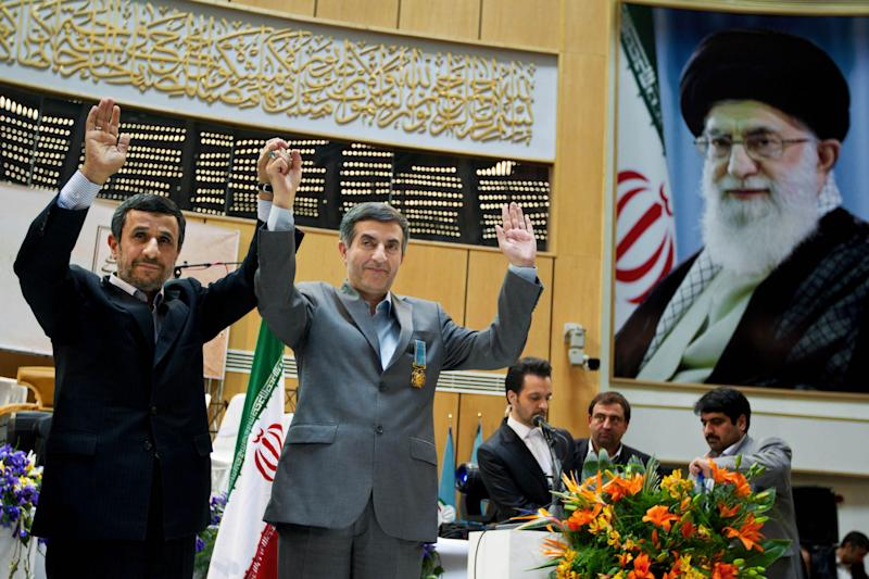 In this Sunday, March 10, 2013 photo, Iranian President Mahmoud Ahmadinejad, left, holds hands with chief of staff Esfandiari Rahim Mashaei, during a press conference in Tehran, Iran. In the waning months of Ahmadinejad's presidency weakened by years of internal battles with the ruling clerics  there appears no bigger priority than attempting one last surprise. It's built around rehabilitating the image of Rahim Mashaei and somehow getting him a place among the candidates for the June 14 vote. A poster with the portrait of Iranian supreme leader Ayatollah Ali Khamenei is seen at right. (AP Photo/Fars News Agency, Mohammad Hassanzadeh)