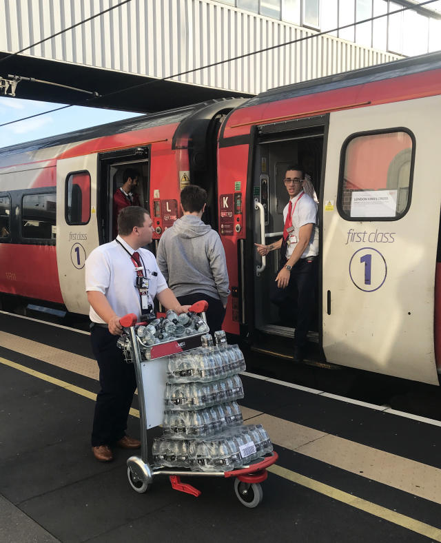 A LNER staff member pushes a trolley of bottled water at Peterborough station, as passengers wait for news during travel disruption on the East Coast mainline (PA)