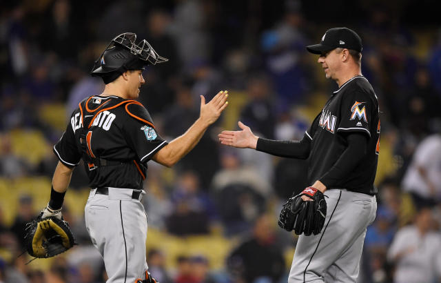 Miami Marlins catcher J.T. Realmuto, left, and relief pitcher Brad Ziegler congratulate each other after the Marlins defeated the Los Angeles Dodgers 3-2 in a baseball game Tuesday, April 24, 2018, in Los Angeles. (AP Photo/Mark J. Terrill)