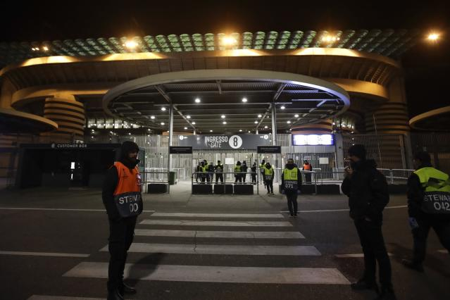 Stewards stand at a gate of the San Siro stadium in Milan, Italy, Thursday, Feb. 27, 2020. Ludogorets is playing Italian club Inter Milan in a Europa League soccer match on Thursday that is scheduled to go ahead in an empty stadium due to the coronavirus outbreak. (AP Photo/Luca Bruno)
