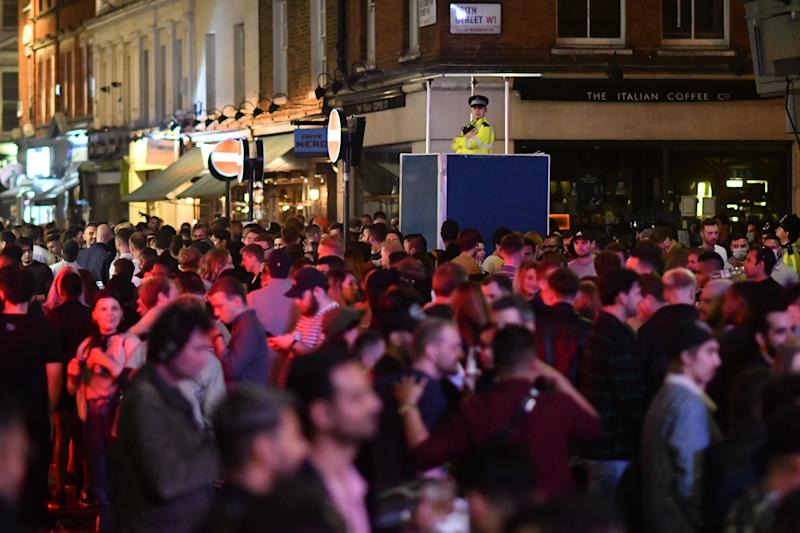 A police officer watches on from an elevated position as revellers drink in the street outside the bars in the Soho area of London on July 4, 2020, as restrictions are further eased during the novel coronavirus COVID-19 pandemic. - Pubs in England reopen on Saturday for the first time since late March, bringing cheer to drinkers and the industry but fears of public disorder and fresh coronavirus cases. (Photo by JUSTIN TALLIS / AFP) (Photo by JUSTIN TALLIS/AFP via Getty Images)