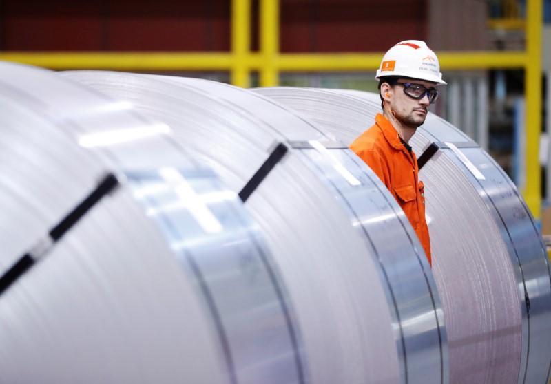 FILE PHOTO: A worker looks at rolls of steel at the ArcelorMittal Dofasco steel plant in Hamilton