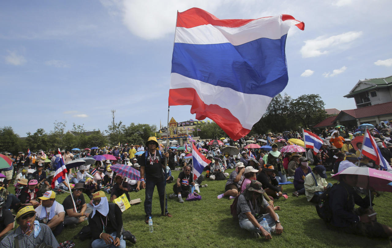 Anti-government protesters with Thai national flags sit at the Royal Thai Army compound in Bangkok, Thailand, Friday, Nov. 29, 2013. The protesters stormed into the national army headquarters on Friday, breaking into their latest high-profile target in a bid to topple Prime Minister Yingluck Shinawatra. (AP Photo/Sakchai Lalit)